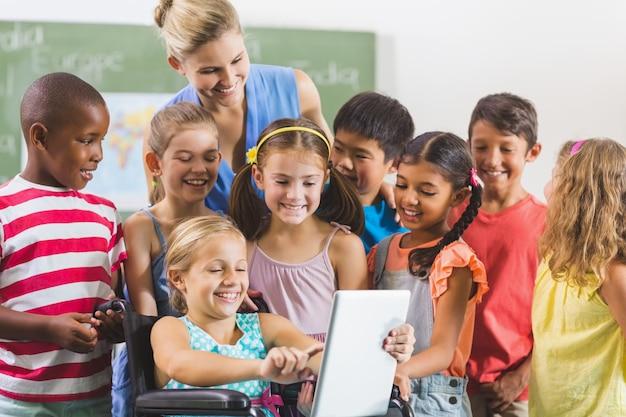 Insegnante e bambini che utilizzano la tavoletta digitale