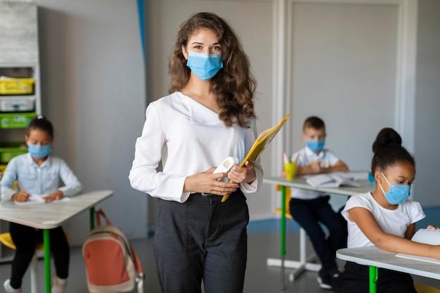 Insegnante e studente che indossano maschere facciali