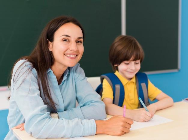 Insegnante e studente seduto in classe