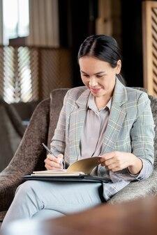 Insegnante elegante abbastanza giovane che controlla i quaderni dei suoi studenti mentre è seduto in poltrona in caffè dopo il lavoro