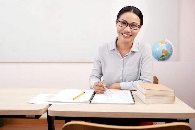 Insegnante femminile asiatica sorridente che si siede allo scrittorio in aula e che scrive in taccuino