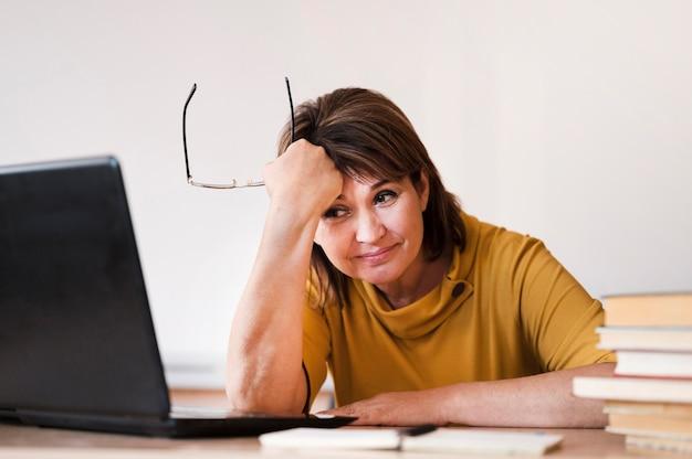 Insegnante femminile con laptop stanco