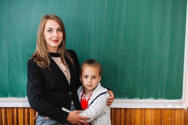 Insegnante femminile con ragazza studentessa in piedi e coccole
