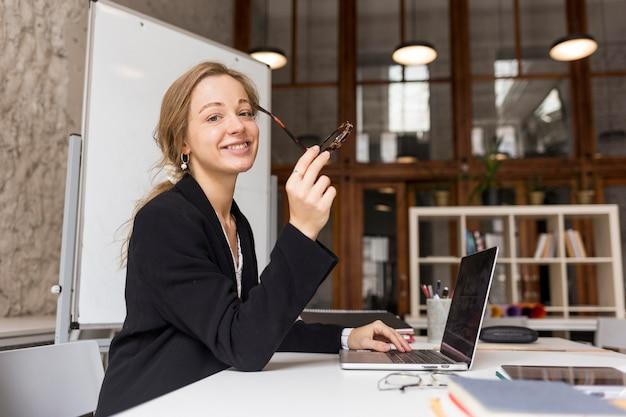 Insegnante femminile di vista laterale con il computer portatile