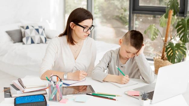 Insegnante femminile e ragazzo sveglio che imparano a casa