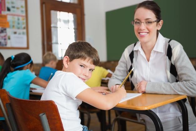 Insegnante grazioso che aiuta allievo in aula che sorride alla macchina fotografica