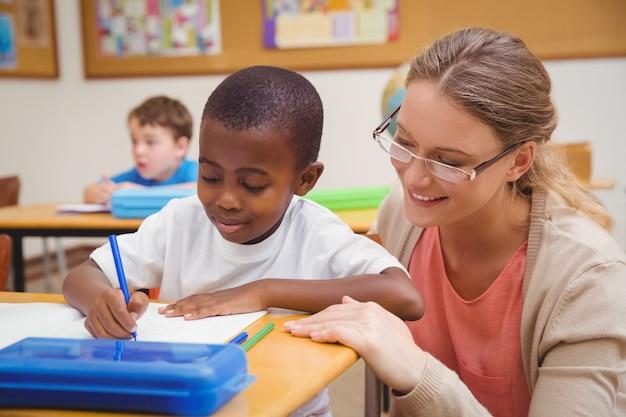 Insegnante grazioso che aiuta allievo in aula
