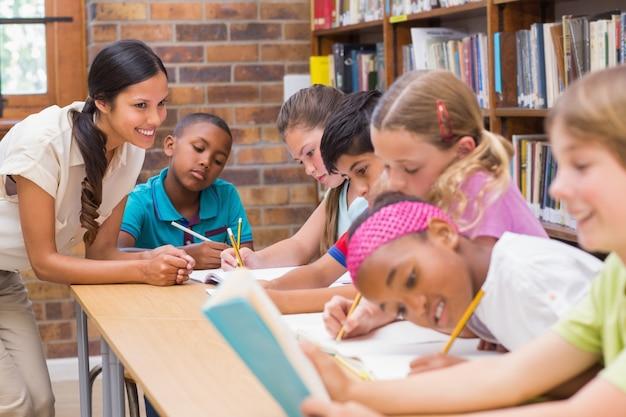 Insegnante grazioso che aiuta gli allievi in biblioteca