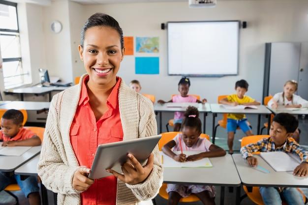 Insegnante in posa davanti alla classe con tablet pc