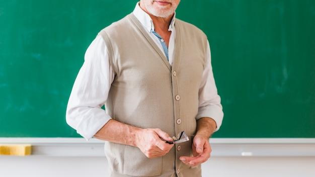Insegnante maschio senior con gli occhiali contro la lavagna