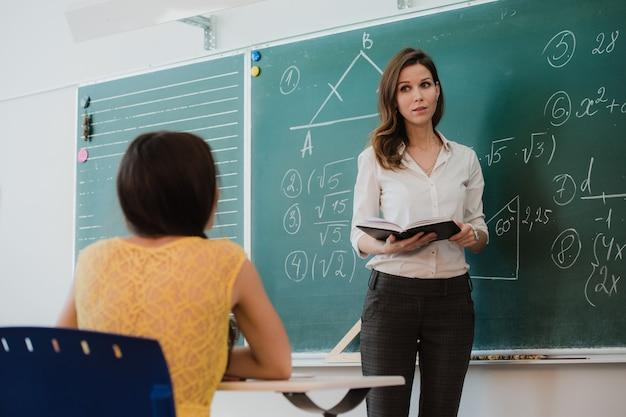 Insegnante o docente o educatore mentre impartisce lezioni di fronte a una lavagna o a un foglio di carta ed educa o insegna a studenti o alunni o compagni in una scuola o in una classe