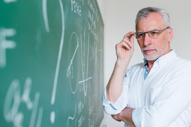Insegnante per la matematica invecchiato concentrato che esamina lavagna