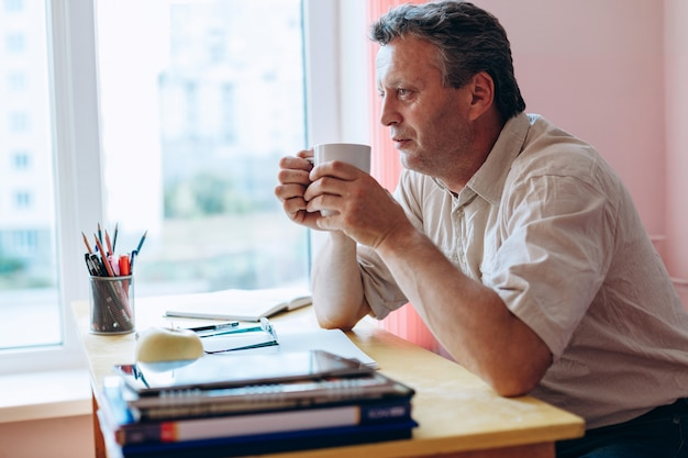 Insegnante seduto al tavolo con una tazza in classe e riposo.