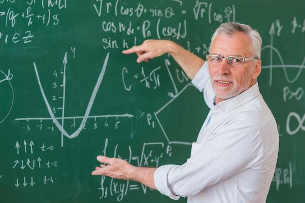 Insegnante senior in vetri che spiega esempio di matematica sulla lavagna verde