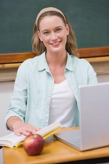 Insegnante sorridente alla sua scrivania