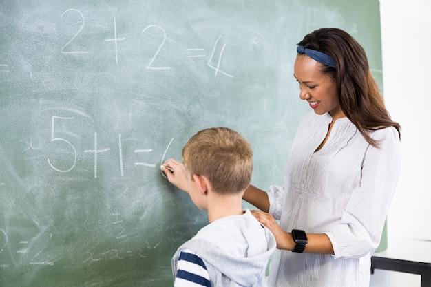 Insegnante sorridente che assiste ragazzo nel fare aggiunta sulla lavagna