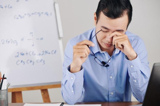 Insegnante strofinando gli occhi stanchi