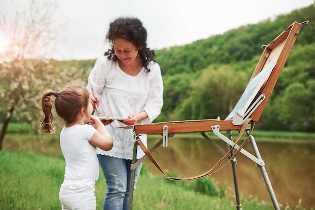 Insegnare alla nipote a dipingere. nel parco naturale