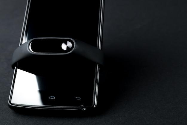 Inseguitore e smartphone di forma fisica sul nero. braccialetto sportivo e smartphone.
