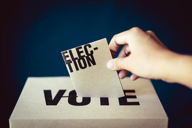 Inserimento di carta di elezione in scatola di voto, concetto di democrazia, retro tono