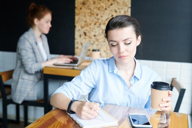 Inserzionista creativo pensieroso serio che si siede al tavolo in una piccola caffetteria e prende appunti nel diario mentre si lavora al progetto di marketing