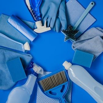 Insieme blu degli strumenti e degli strumenti di pulizia per pulizie di primavera nella casa sul blu