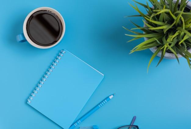 Insieme blu dello spazio di lavoro del blocco note, della penna, degli occhiali e della tazza di caffè, vista superiore