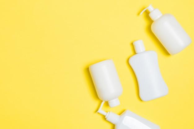 Insieme dei contenitori cosmetici bianchi isolati su fondo giallo, vista superiore con lo spazio della copia. gruppo di contenitori per bottiglie in plastica per la cura del corpo