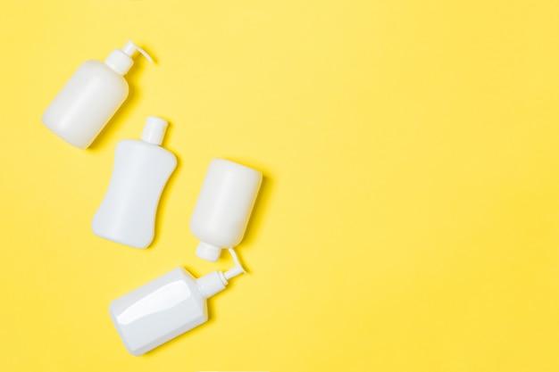 Insieme dei contenitori cosmetici bianchi su fondo giallo con copyspace