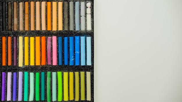 Insieme dei pastelli pastelli multicolori nella scatola di openartist su un fondo bianco, vista superiore.