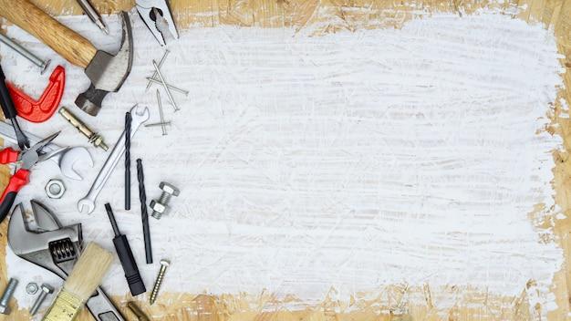 Insieme dei rifornimenti degli strumenti per il costruttore di riparazione della casa su legno dipinto bianco con lo spazio della copia