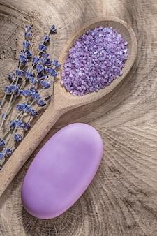 Insieme del pezzo di sapone di cristallo profumato della lavanda del sale marino di legno del cucchiaio di legno sul concetto di sanità di legno del bordo