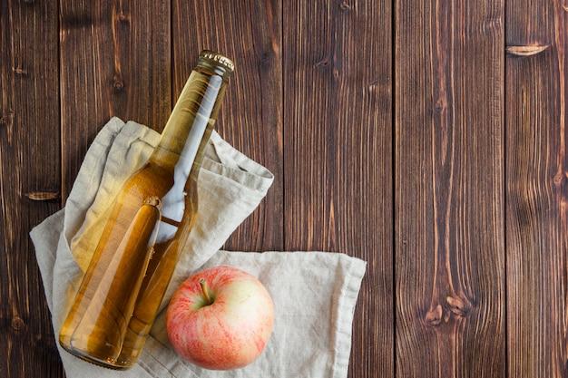 Insieme del succo e della mela di mele su un panno e su un fondo di legno. vista dall'alto. spazio per il testo