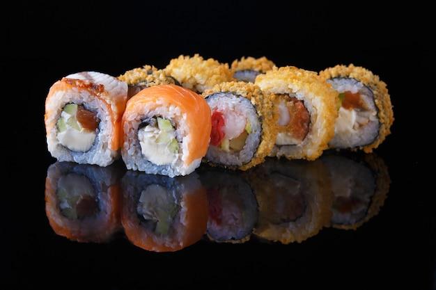 Insieme delizioso del rotolo di sushi con il pesce su un fondo nero con la riflessione menu e ristorante