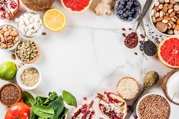 Insieme dell'alimento organico di dieta sana, supercibi - fagioli, legumi, noci, semi, verdi, frutta e verdure ... spazio bianco della copia del fondo. cornice vista dall'alto