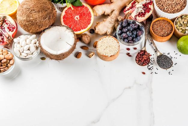 Insieme dell'alimento organico di dieta sana, supercibi - fagioli, legumi, noci, semi, verdi, frutta e verdure ... spazio bianco della copia del fondo. vista dall'alto