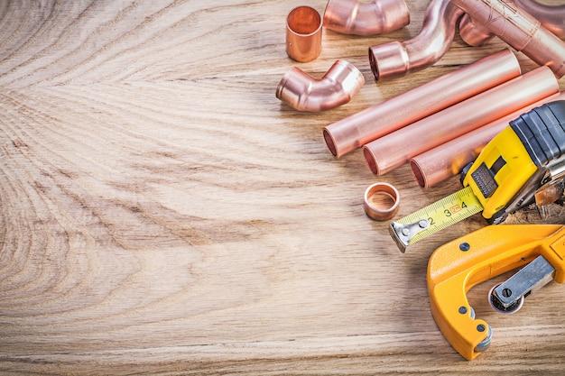 Insieme della linea di nastro di rame dei connettori della taglierina della tubatura dell'acqua sul concetto del brassware dell'impianto idraulico del bordo di legno