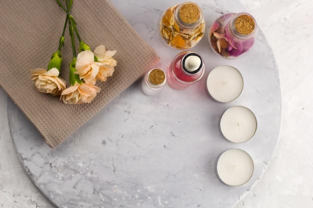 Insieme della stazione termale, bottiglie, candele e spazio superiore della copia del fondo di marmo di vista superiore dei fiori