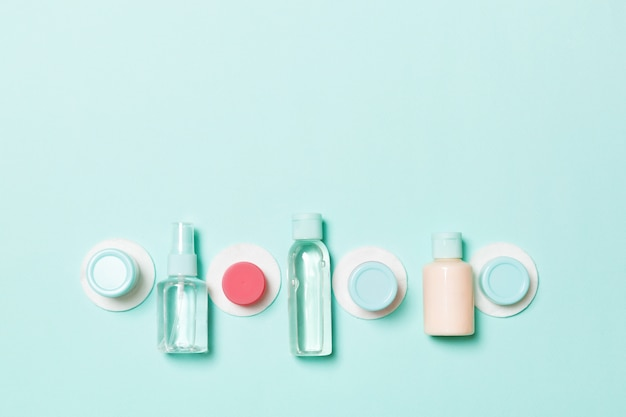 Insieme delle bottiglie cosmetiche di dimensione di viaggio su fondo blu. lay piatto di vasetti di crema