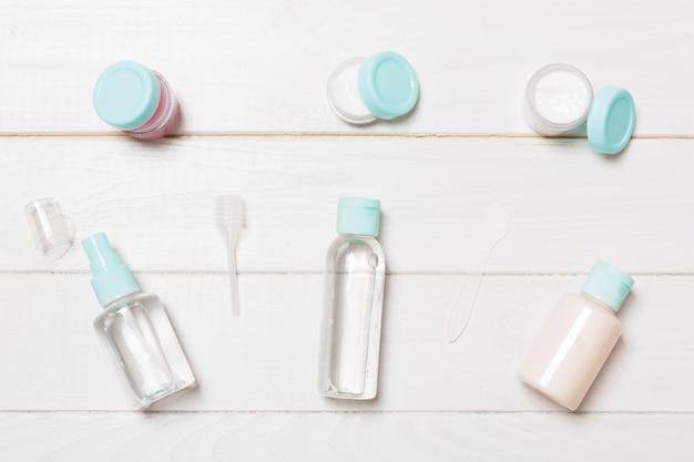 Insieme delle bottiglie cosmetiche di dimensione di viaggio su fondo di legno bianco. lay piatto di vasetti di crema. vista dall'alto dello stile bodycare
