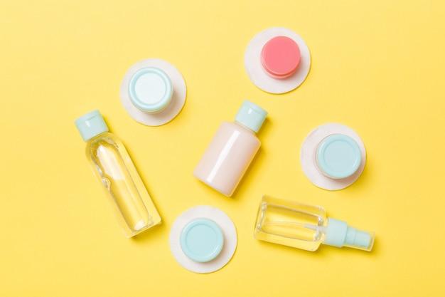 Insieme delle bottiglie cosmetiche di dimensione di viaggio su giallo