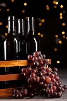 Insieme delle bottiglie di vino e dell'uva con il fondo del bokeh