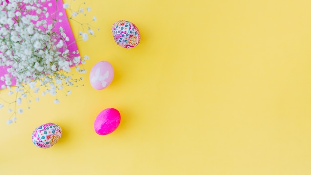 Insieme delle uova di pasqua rosa vicino ai fiori sul tovagliolo