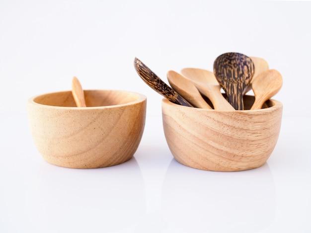 Insieme dello spuntino con la tazza, la ciotola e il cucchiaio di legno fatti a mano dalla tailandia, isolati su superficie bianca.
