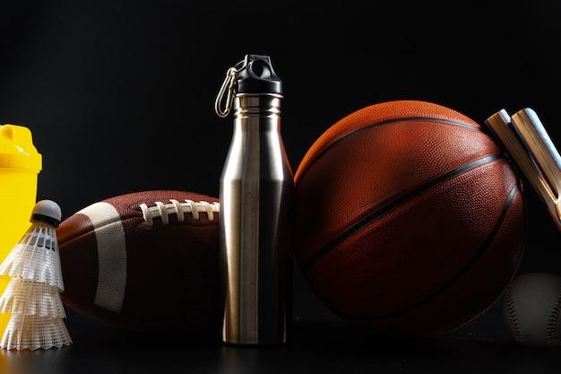 Insieme di attrezzature sportive e strumenti sulla fine nera del fondo su