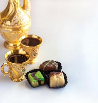 Insieme di caffè arabo dorato tradizionale di natura morta con dallah, tazza e caramelle al cioccolato.