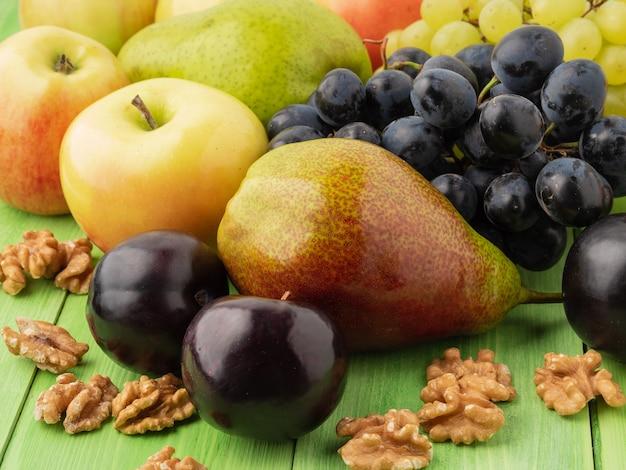 Insieme di frutti su una tavola di legno verde - mele, pere, uva, prugne, noci