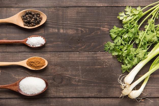 Insieme di raccolta di spezie su cucchiai di legno e verdure.