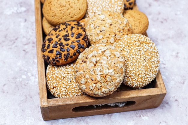 Insieme di vari biscotti di stile americano in vassoio di legno su fondo in cemento leggero. frollini con semi di sesamo, burro di arachidi, fiocchi d'avena e biscotti con gocce di cioccolato.