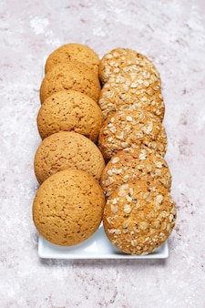 Insieme di vari biscotti in stile americano su uno sfondo di cemento chiaro. frollini con coriandoli, semi di sesamo, burro di arachidi, fiocchi d'avena e biscotti al cioccolato.